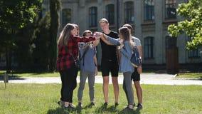 Estudantes universitário felizes com mãos na pilha video estoque