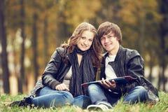 Estudantes universitário felizes no gramado do terreno fora Fotos de Stock Royalty Free