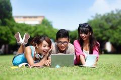 Estudantes universitário felizes que usam o computador Imagem de Stock