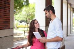 Estudantes universitário felizes que usam o computador fotografia de stock