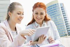 Estudantes universitário novas de sorriso que usam a tabuleta digital contra a construção imagem de stock