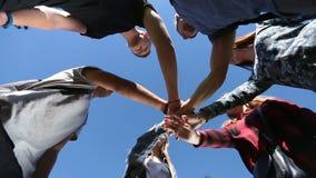 Estudantes universitário que empilham as mãos no gramado do parque video estoque