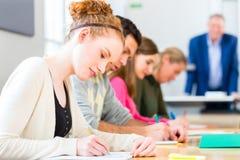 Estudantes universitário que escrevem o teste ou o exame