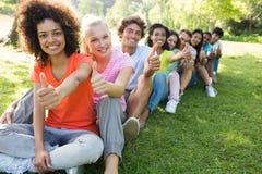 Estudantes universitário que gesticulam os polegares acima Imagem de Stock