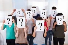 Estudantes universitário que guardam sinais do ponto de interrogação foto de stock