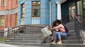 Estudantes universitário que olham o mapa, construção de assento em escadas, viagem sightseeing video estoque