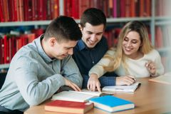 Estudantes universitário que sentam-se junto na tabela com livros e portátil Os jovens felizes que fazem o grupo estudam na bibli imagem de stock