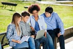 Estudantes universitário que usam o portátil no terreno Fotos de Stock
