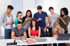 Estudantes universitário que usam telefones celulares Foto de Stock Royalty Free