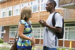 Estudantes universitários masculinos e fêmeas que falam no terreno Fotos de Stock Royalty Free