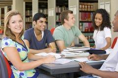 Estudantes universitários que estudam junto em uma biblioteca Imagem de Stock
