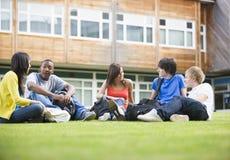 Estudantes universitários que sentam-se e que falam no gramado fotos de stock