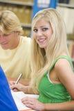 Estudantes universitários que trabalham na biblioteca Fotos de Stock Royalty Free