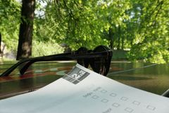 Estudiando con un libro en el parque, gafas de sol en la tabla imagenes de archivo
