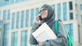 Estudiante árabe alegre que habla en la situación del teléfono en campus universitario almacen de video