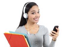 Estudiante árabe que escucha la música y que sostiene carpetas Imagenes de archivo