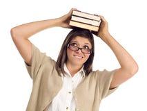 Estudiante étnico con los libros en su cabeza sobre blanco Foto de archivo