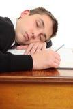 Estudiante aburrido cansado en el escritorio Fotografía de archivo