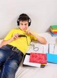 Estudiante aburrido con un libro y un teléfono móvil Fotografía de archivo libre de regalías