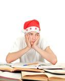 Estudiante aburrido en el sombrero de Santas Imagen de archivo
