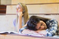 Estudiante aburrido que escucha mientras que el dormir del compañero de clase Foto de archivo