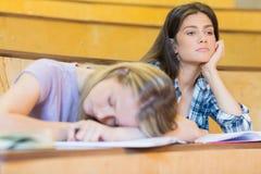 Estudiante aburrido que escucha mientras que el dormir del compañero de clase Fotografía de archivo libre de regalías