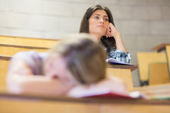 Estudiante aburrido que escucha mientras que el dormir del compañero de clase Fotos de archivo