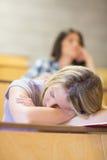 Estudiante aburrido que escucha mientras que el dormir del compañero de clase Fotografía de archivo