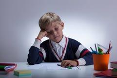 Estudiante aburrido que se sienta en el escritorio Fotografía de archivo libre de regalías