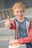 Estudiante acertado con el pulgar-para arriba de la demostración de los libros Foto de archivo
