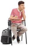 Estudiante adolescente aburrido que se sienta en una silla de la escuela Foto de archivo