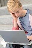 Estudiante adolescente aburrido que usa el ordenador portátil Fotografía de archivo libre de regalías