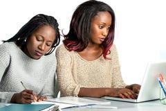 Estudiante adolescente africano lindo que trabaja en el ordenador portátil con el amigo Imagenes de archivo