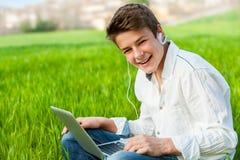 Estudiante adolescente con el ordenador portátil al aire libre. Fotos de archivo libres de regalías
