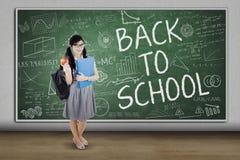 Estudiante adolescente con el texto de nuevo a escuela Foto de archivo libre de regalías