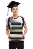 Estudiante adolescente con la pila de la tenencia del sombrero de la graduación de libros Imagen de archivo