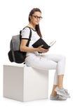 Estudiante adolescente con un libro que se sienta en un cubo Fotografía de archivo