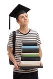 Estudiante adolescente con un sombrero de la graduación que sueña despierto Foto de archivo libre de regalías