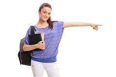 Estudiante adolescente con una mochila y los libros que señala a la derecha Imagen de archivo