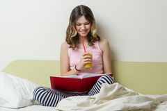 Estudiante adolescente de la High School secundaria de la muchacha que lee un libro de texto que se sienta en casa en cama Imagenes de archivo