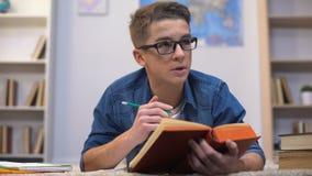 Estudiante adolescente del collage que prepara la asignación, aprendiendo idioma extranjero, vocabulario almacen de video