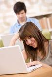 Estudiante - adolescente dos con la computadora portátil en sala de estar Fotos de archivo libres de regalías