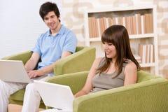 Estudiante - adolescente dos con la computadora portátil en sala de estar Foto de archivo libre de regalías
