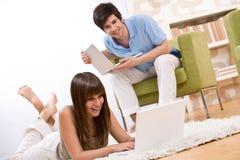 Estudiante - adolescente dos con la computadora portátil en sala de estar Fotografía de archivo