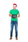 Estudiante adolescente en un sombrero de la Navidad que sostiene una tableta Imagenes de archivo