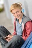 Estudiante adolescente feliz que escucha la música Foto de archivo libre de regalías
