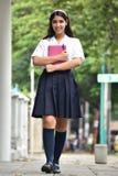 Estudiante adolescente femenina Walking On Sidewalk foto de archivo