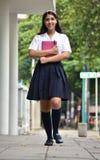 Estudiante adolescente femenina Walking On Sidewalk imagenes de archivo