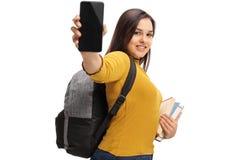 Estudiante adolescente femenino con una mochila y los libros que muestran un teléfono Imagen de archivo libre de regalías