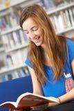 Estudiante adolescente femenino en libro de lectura de la biblioteca Imagen de archivo libre de regalías